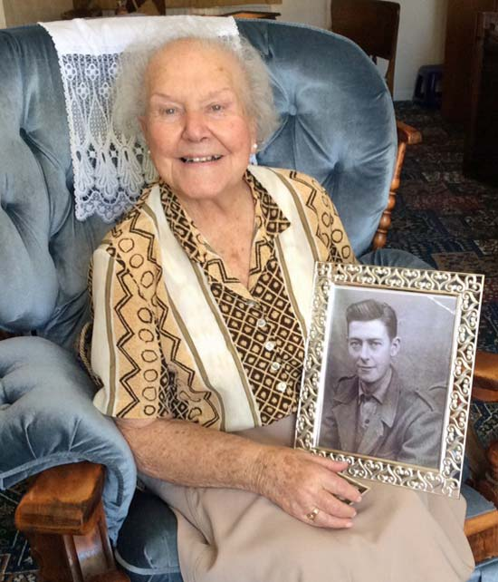 Alma Charnock holding a photo of her late husband Hal